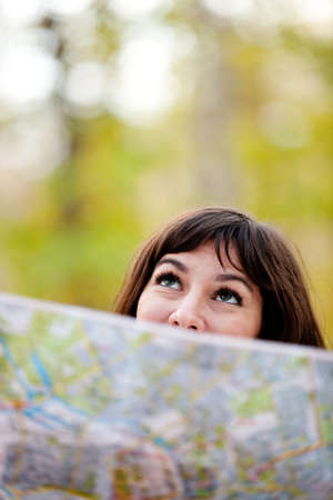Woman exploring outdoors holding a map and looking lost  photo