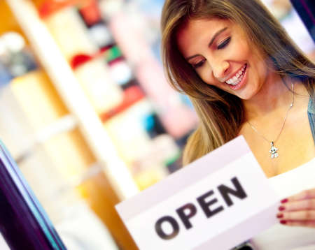 business owner: Woman putting an open sign at the door of a business store