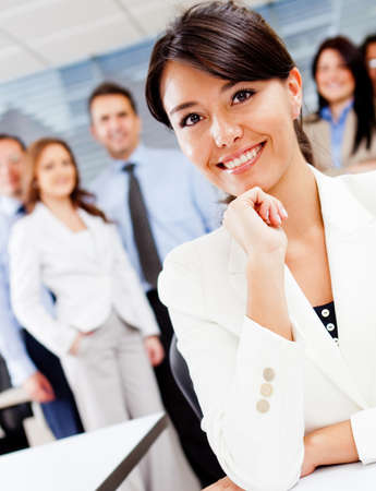 Confident corporate female worker with a group at the background photo