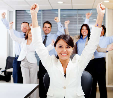 executives: Business woman leading a successful group with arms up Stock Photo