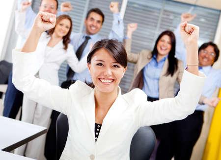 gente celebrando: Mujer de negocios con los brazos frente de un equipo exitoso