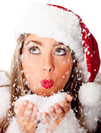 Female Santa holding snow in her hands and blowing - isolated over a white background photo