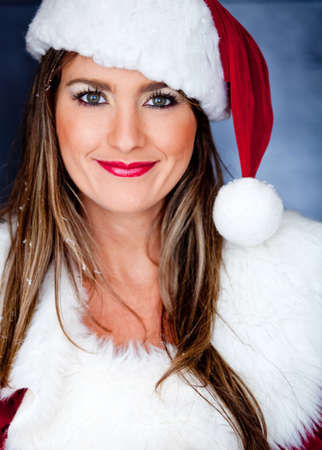 mrs: Portrait of a beautiful female Santa over a blue background Stock Photo