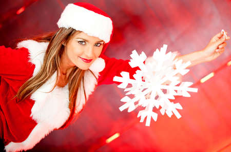 Beautiful female Santa hanging a snowflake and smiling  photo