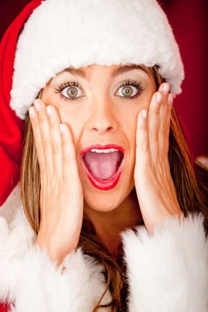 Portrait of a beautiful female Santa looking surprised over Christmas  photo