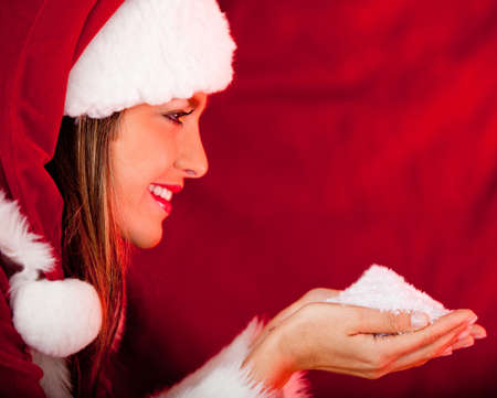 Beautiful female Santa holding snow in her hands and smiling photo