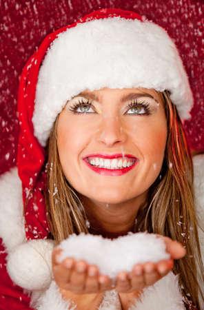Gorgeous female Santa under falling snow and smiling photo
