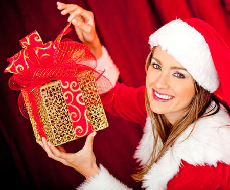 Female Santa opening a Christmas gift and smiling  photo