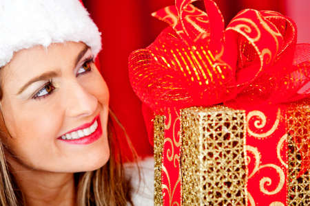 Beautiful female Santa celebrating Christmas with a gift  photo
