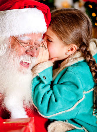 Little girl telling a secret to Santa Claus photo