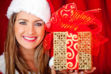 Gorgeous Mrs. Claus celebrating Christmas and holding a present photo