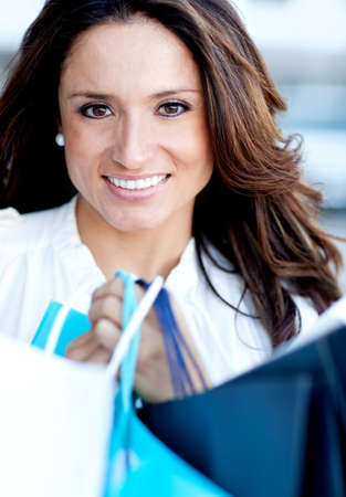 Beautiful woman holding shopping bags and smiling photo