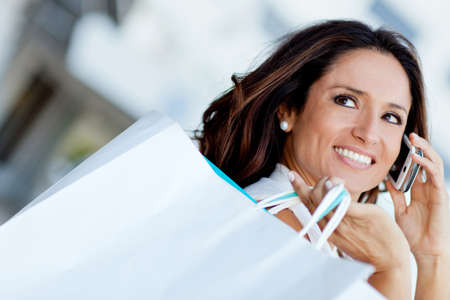 Shopping woman talking on the phone and holding bags Stock Photo - 11936023