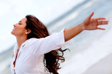 huir: Mujer que se relaja en la playa con los brazos abiertos disfrutando de su libertad Foto de archivo