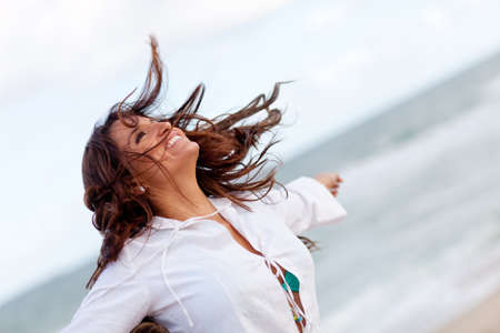 retreat: Woman enjoying the windy weather at the beach and relaxing