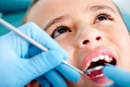 Kid at the dentist getting his teeth checked  photo