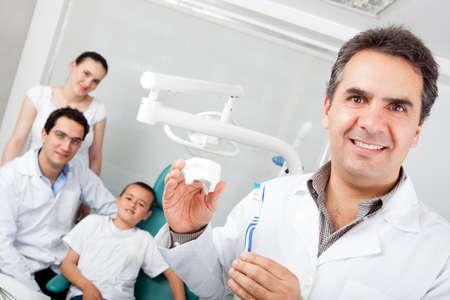 prothese: Zahnarzt im Besitz einer Zahnb�rste und zeigt, wie man sie richtig einsetzen