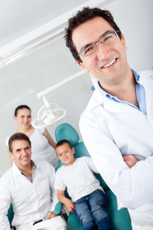 Pediatric male dentist with his team and a young patient photo