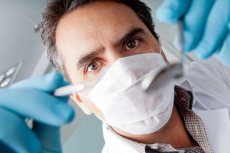 Professional male dentist holding instruments and wearing facemask  photo