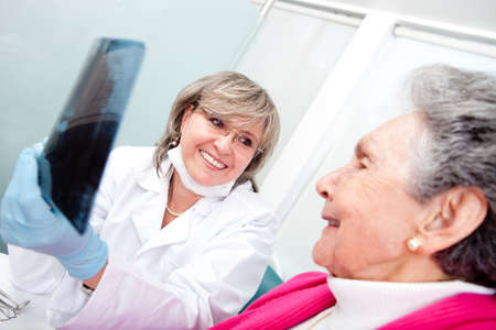 Dentist with an elder female patient looking at an x-ray photo