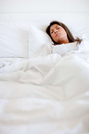 Woman sleeping in bed looking very comfortable  photo
