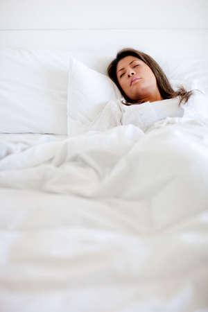 Woman sleeping in bed looking very comfortable  photo