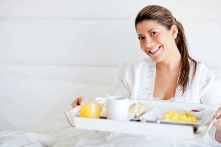 Beautiful happy woman having breakfast in bed  photo