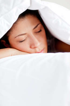 catnap: Woman in bed sleeping under the cover