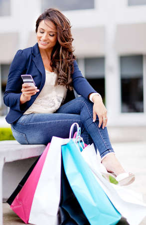 commerce communication: Shopping woman texting on her mobile phone with bags - outdoors