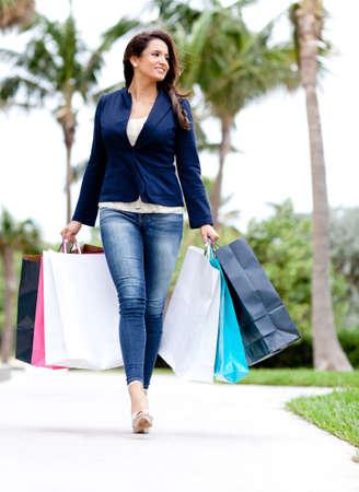 outlets: Compras mujer caminando al aire libre y las bolsas de la celebraci�n de