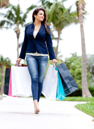 shopping malls: Shopping woman walking outdoors and holding bags