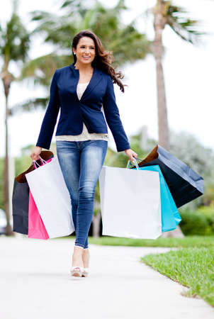 Beautiful female shopper with bags walking outdoors  photo