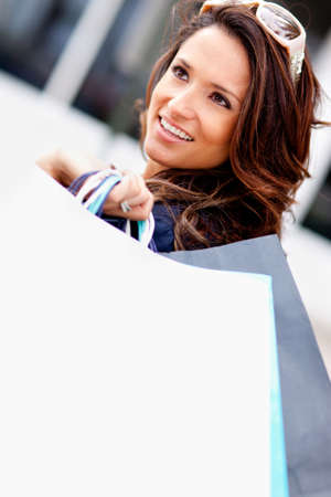 Fashionable shopping woman holding bags and smiling  photo