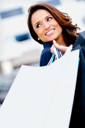 Happy female shopper smiling and carrying bags Stock Photo - 11936021
