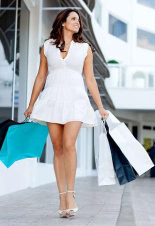 skirts: Compras de la mujer hermosa caminando en el centro comercial con bolsas