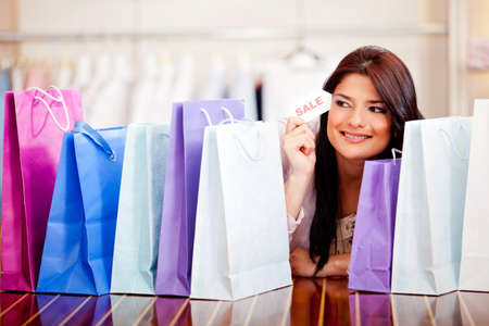 Beautiful woman with shopping bags holding a sale tag  Stock Photo - 11981108
