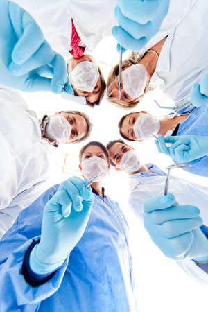 quirurgico: Grupo de los dentistas que sostienen los instrumentos m�dicos en el hospital