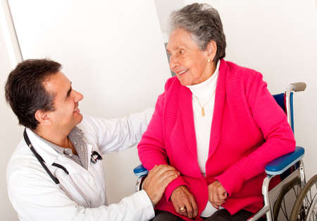 Elder woman sitting in a wheelchair at the hospital talking to the doctor  photo