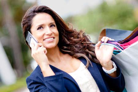 chicas de compras: Compras mujer hablando por tel�fono y celebraci�n de las bolsas Foto de archivo