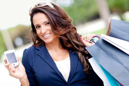 compras compulsivas: Mujer de compras con un teléfono móvil en la mano y sosteniendo bolsas