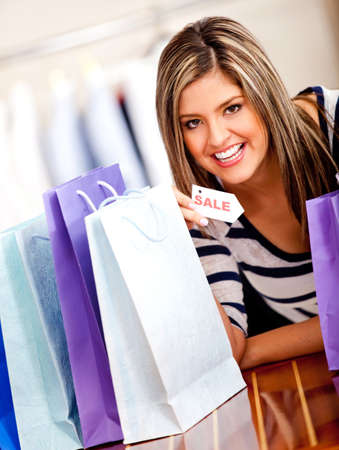 Happy shopping woman holding a sale tag  photo
