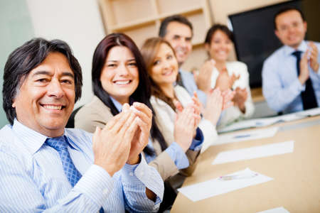clap: Successful business team in a meeting applauding