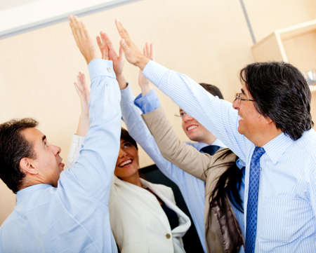 Successful business group giving a high-five at the office Stock Photo - 12027498