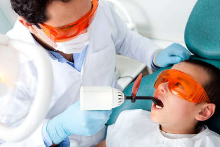 oral care: Dentist fixing a cavity on a boy using the laser light Stock Photo
