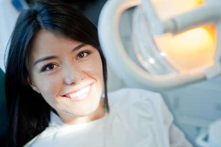 odontologia: Mujer joven retrato de visitar al dentista y sonriente