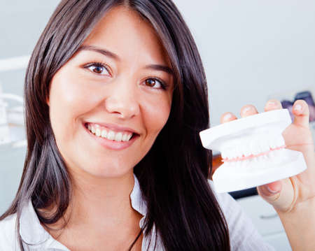orthodontics: Woman holding a teeth sample or prosthesis at the dentist
