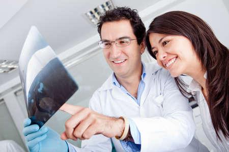 orthodontics: Dentista mirando una radiograf�a a un paciente Foto de archivo