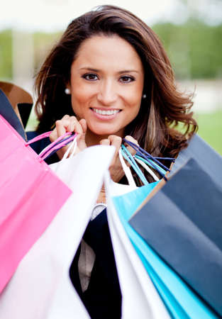 outlets: Beautiful woman shopping holding her purchases and smiling
