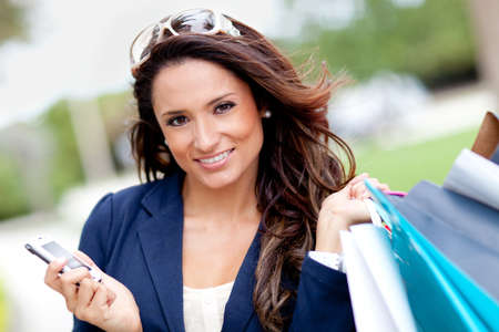 commerce: Woman holding cell phone while shopping Stock Photo