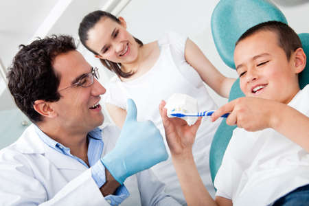 male dentist: Dentist showing a boy how to brush his teeth properly